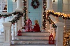 Niña en el vestido rojo que se sienta en el mirador de la casa adornada, luces de la Navidad, ` s Eve del Año Nuevo están después foto de archivo libre de regalías