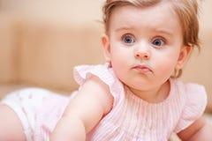 Niña en el vestido rosado que miente en el sofá Fotografía de archivo libre de regalías