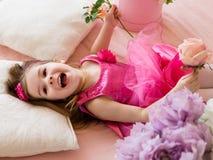 Niña en el vestido rosado que miente en el sofá, riendo mientras que playin Fotografía de archivo