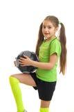 Niña en fútbol que juega uniforme del verde con la bola Fotografía de archivo