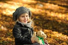 Niña en hojas de otoño Fotografía de archivo