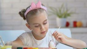 Niña en huevo lindo del colorante de la venda con la pintura brillante, escuela de arte para los niños metrajes