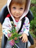 Niña en la bicicleta con un ramo de flores fotos de archivo