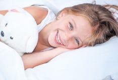 Niña en la cama con el oso de peluche Fotos de archivo libres de regalías