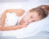 Niña en la cama con el oso de peluche Fotografía de archivo libre de regalías