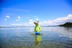 Niña en la camisa verde que juega en el agua Playa de Whangarei Imagen de archivo libre de regalías