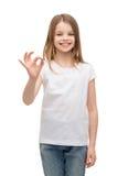 Niña en la camiseta blanca que muestra gesto aceptable Imagenes de archivo