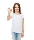 Niña en la camiseta blanca que muestra gesto aceptable Foto de archivo libre de regalías