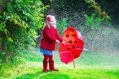 Niña en la chaqueta roja que juega en lluvia del otoño Imágenes de archivo libres de regalías