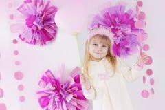 Niña en la fiesta de cumpleaños adornada rosada con el globo Imagen de archivo
