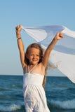 Niña en la orilla de mar que juega con un pañuelo en el viento Foto de archivo libre de regalías