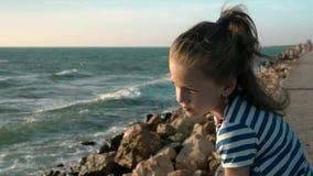 Niña en la playa día ventoso en la puesta del sol Soledad del concepto almacen de video