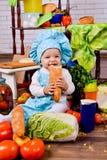 Niña en la ropa del cocinero con la barra de pan Imagen de archivo