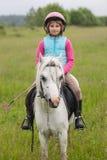 Niña en la ropa para montar una agudeza que se sienta del caballo en un caballo al aire libre Imagen de archivo libre de regalías