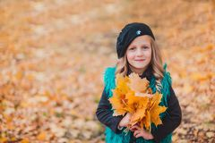 Niña en las hojas de la tenencia del otoño La niña en la boina marrón en parque del otoño fotos de archivo libres de regalías