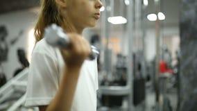 Niña en las pesas de gimnasia involucradas con gimnasio almacen de metraje de vídeo