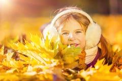 Niña en los earflaps que juegan con las hojas de otoño Foto de archivo libre de regalías