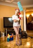 Niña en los guantes de goma que presentan con la fregona en la sala de estar Imagen de archivo libre de regalías