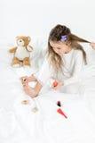 Niña en los pijamas y los bigudíes que aplican esmalte de uñas a las uñas del pie que se sientan en cama Imagen de archivo libre de regalías