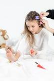 Niña en los pijamas y los bigudíes que aplican esmalte de uñas a las uñas del pie que se sientan en cama Fotografía de archivo libre de regalías