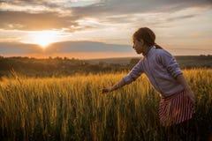 Niña en los rayos de la puesta del sol en el campo Puesta del sol colorida sobre campo de trigo con la llamarada de la lente fotografía de archivo libre de regalías