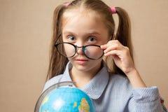 Niña en los vidrios que sostienen el globo Foto de archivo libre de regalías