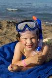 Niña en máscara del equipo de submarinismo en la playa Imagenes de archivo