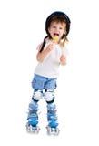 Niña en pcteres de ruedas con el caramelo Imagen de archivo libre de regalías