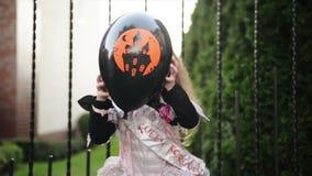Niña en princesa Costume Holding un globo negro Ella parece muy feliz porque el hoy es día de fiesta de Halloween almacen de video