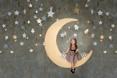 Niña en sentarse en la luna grande El pequeño soñar de la muchacha Imágenes de archivo libres de regalías