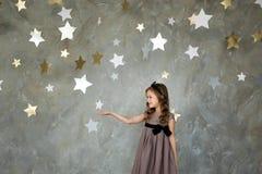 Niña en sentarse en la luna grande El pequeño soñar de la muchacha Foto de archivo
