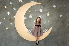 Niña en sentarse en la luna grande El pequeño soñar de la muchacha Foto de archivo libre de regalías