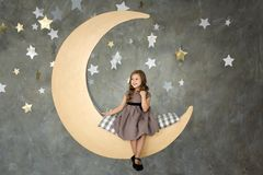 Niña en sentarse en la luna grande El pequeño soñar de la muchacha Imagen de archivo