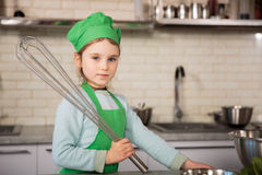 Niña en sombrero del cocinero en la cocina Fotografía de archivo