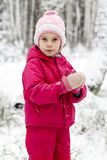 Niña en sus brazos en la nieve, en el parque del invierno Juego en la nieve Diversión del invierno para los niños está entonando imagenes de archivo