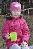 Niña en té de consumición del bosque de la primavera Foto de archivo