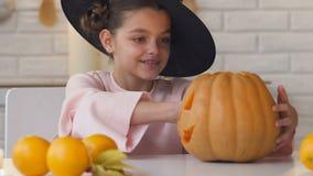 Niña en traje de la bruja con la calabaza del enchufe que muestra los pulgares-para arriba, Halloween metrajes