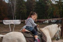 Niña en un caballo blanco en el parque Imágenes de archivo libres de regalías