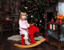 Niña en un caballo del juguete Imagenes de archivo