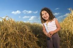 Niña en un campo de trigo Fotos de archivo libres de regalías