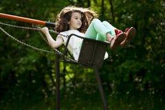 Niña en un oscilación en el parque del verano Foto de archivo libre de regalías