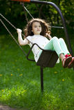 Niña en un oscilación en el parque del verano Fotos de archivo libres de regalías