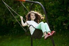 Niña en un oscilación en el parque del verano Fotografía de archivo