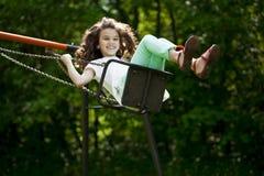 Niña en un oscilación en el parque del verano Imagenes de archivo