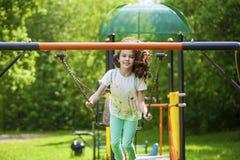 Niña en un oscilación en el parque del verano Imagen de archivo libre de regalías