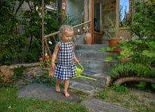 Niña en un pequeño jardín con el pote de riego verde imagen de archivo