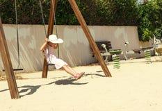 Niña en un sombrero blanco grande que se divierte en un oscilación en el día soleado Fotografía de archivo