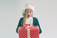 Niña en un sombrero de la Navidad que sostiene los regalos en el fondo blanco Le deseamos una Feliz Navidad y una Feliz Año Nuevo Imagen de archivo