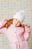 Niña en un sombrero rosado y un suéter Imagen de archivo