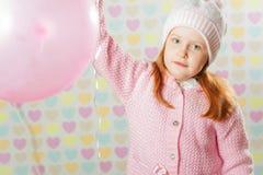 Niña en un sombrero rosado y un suéter Imagen de archivo libre de regalías